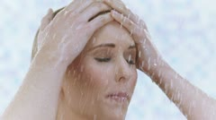 Young woman taking a shower in slow motion Stock Footage
