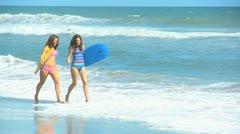 Pretty Girls Splashing Ocean Carrying Body Board Stock Footage