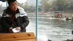 Moving Guilin China Chinese river boat driver steering motor beautiful mountain Stock Footage