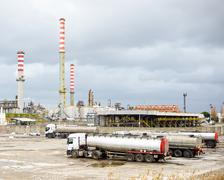 oil refinery industry, smoke stacks and tanker lorry or truck - stock photo