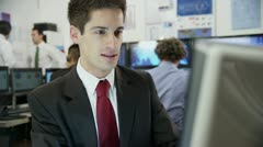Portrait of a young and ambitious stock market trader at work in a busy office - stock footage
