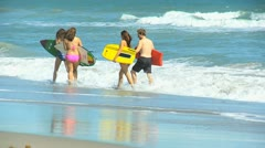 Family Splashing Ocean Carrying Surf Boards Stock Footage