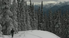 A man snowshoes across a snowy mountainside. Stock Footage