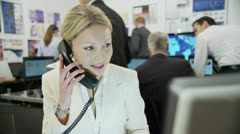 Beautiful female city worker takes a phone call at her desk in a busy office. Stock Footage