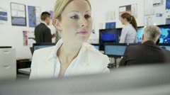 Portrait of beautiful female city worker at her desk in a busy office. Stock Footage