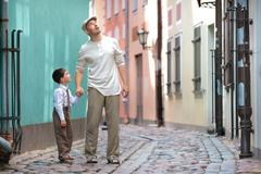 Father and son walking outdoors in city Stock Photos