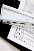 preparing taxes - check and forms on keyboard - stock photo