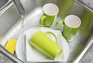 Washing green cups and plates in the kitchen sink Stock Photos