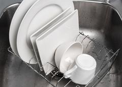 Dishes drying on a rack in the kitchen sink Stock Photos