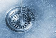 Water running into kitchen sink drain Stock Photos