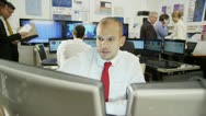 Young and ambitious male stock market trader hard at work in a busy office Stock Footage