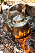 Kettle with water heated on the fire Stock Photos