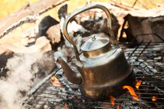 kettle with water heated on the fire - stock photo