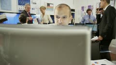Young and ambitious male stock market trader hard at work in a busy office - stock footage