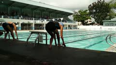 Female Athletic swimmer dive into pool at signal Stock Footage