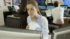Young and ambitious female stock market trader hard at work in a busy office Stock Footage