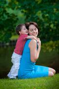 Two years old boy hugs his young mom in park Stock Photos