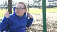 Young boy sitting on swing looking at camera Stock Footage