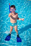 A little boy standing in a pool - stock photo