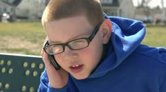 Child using cell phone in park Stock Footage