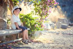 Three years old boy sitting on bench Stock Photos
