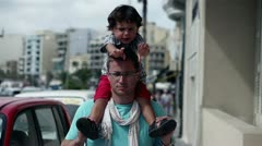 Father carrying son on piggy back ride in the city, slow motion shot at 240fps Stock Footage