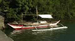 Traditional Filipino banka outrigger fishing boat in a river in Philippines Stock Footage