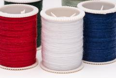Colored spools of string on white background. Stock Photos