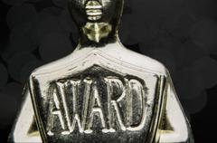 Close up of golden award sheild on black. Stock Photos