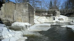 Ice frozen river banks between retro waterfall cascade winter Stock Footage