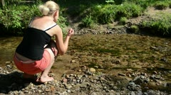 Woman shorts sit stream throw pebble stones flowing water Stock Footage