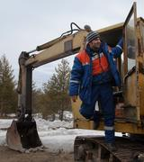 machinist excavator in a good mood - stock photo