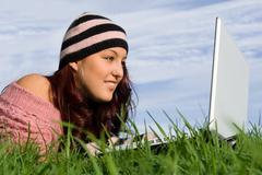 teen outdoor on internet with wifi laptop computer - stock photo