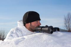 scout in white camouflage coat with binoculars - stock photo