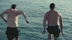 Young men jumping, swimming in the sea, slow motion shot at 240fps Stock Footage