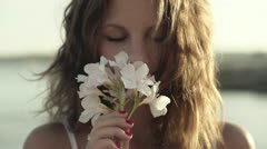 Young woman standing on seashore and smelling flower, slow motion shot at 240fps Stock Footage