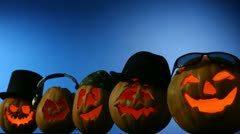 Jack O'Lanterns In Different Headwear On Blue Background Stock Footage