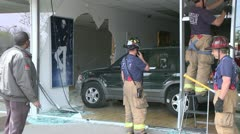 CAR AUTOMOBILE CRASHES INTO BUILDING EMERGENCY CREWS DRIVES IT OUT HD VIDEO 1080 Stock Footage