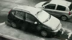 Car passes parked car in snow Stock Footage