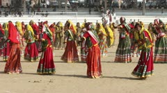Indian girls in colorful ethnic attire dancing at Pushkar camel fair India - stock footage