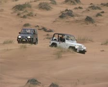 4x4s driving in dunes Stock Footage