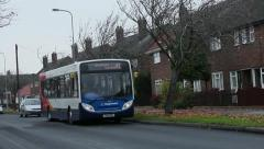 Bus in residential area - with focus play at start Stock Footage