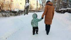 Boy and his mother are walking together in the park. - stock footage