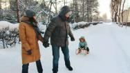 Stock Video Footage of Parents are sledging his son along the alley