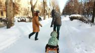 Stock Video Footage of Family is sledging their son along the alley