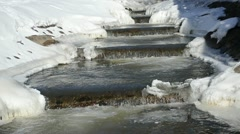 Brook stream stairs icy bank cascade waterfall beauty winter day Stock Footage