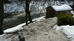 Stone stairs outdoor bathhouse roof covered snow winter river Stock Footage