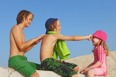 summer vacation kids with sun protection cream - stock photo