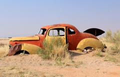 Old and rusty car wreck at the last gaz station before the namib desert Stock Photos
