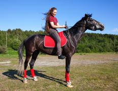Girl on a horse with hair fluttering in the wind Stock Photos